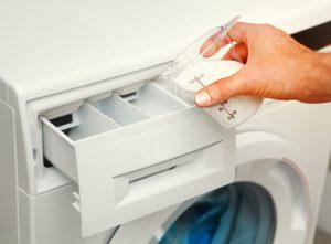 En hand som håller en behållare med tvättmedel.