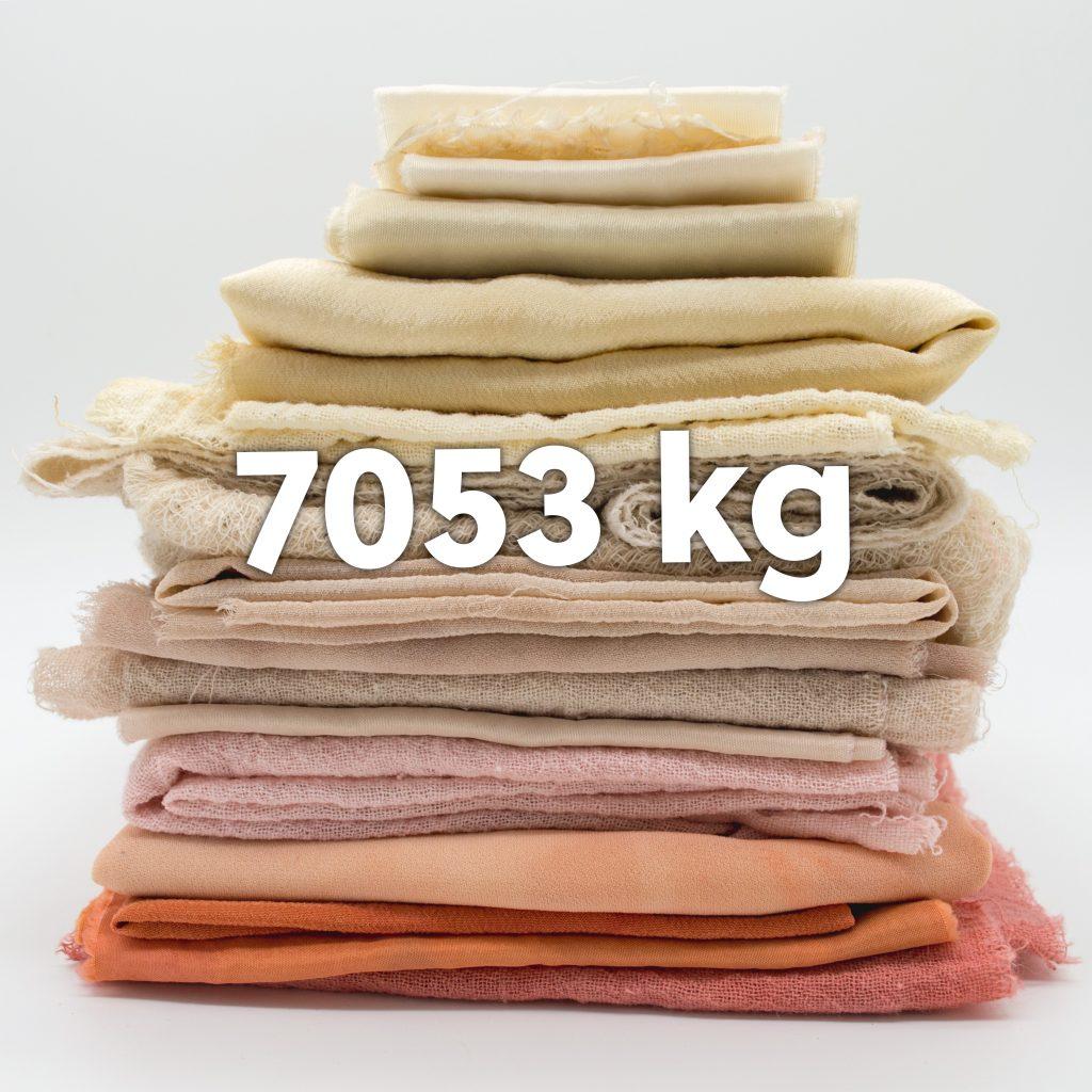 Hög med textilier. Text: 7053 kg.